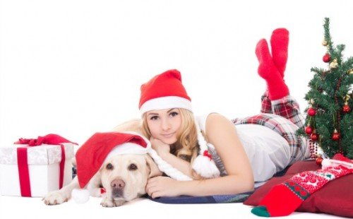 beautiful teenage girl in pajamas lying with dog in santa hat isolated on white background